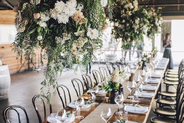 suspension boules végétales aux fleurs au dessus d une table rustique, chemin de table jute, décoration de table mariage campagne chic