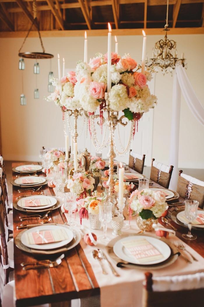 bougeoirs décorées de fleurs rose et blanches en hauteur comme centre de table sur chemin de table blanc sur table bois marron, deco plafond en bois