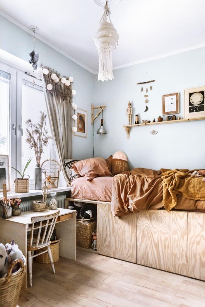 aménagement de petite chambre d'enfant aux murs bleu clair avec meubles en bois et accessoires de style bohème