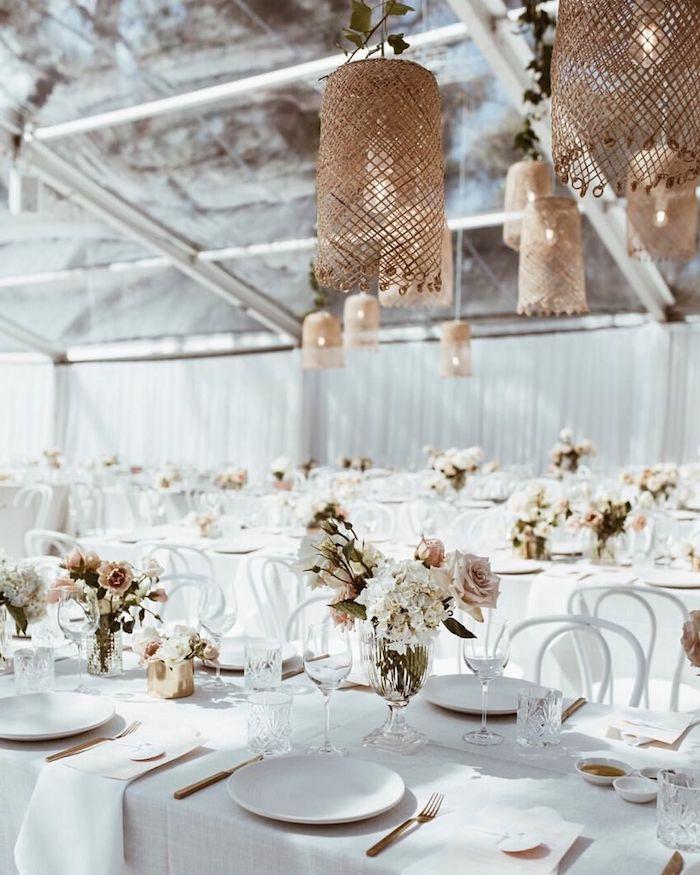 deco suspensions en maillage style bord de mer au dessus de tables blanches avec bouquets de fleurs pales, mariage sur veranda