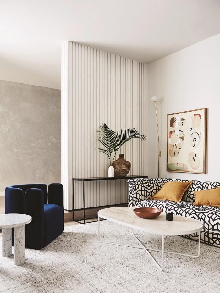 exemple de deco salon moderne aux murs blancs avec pan de mur à effet béton et meubles tendance en velours