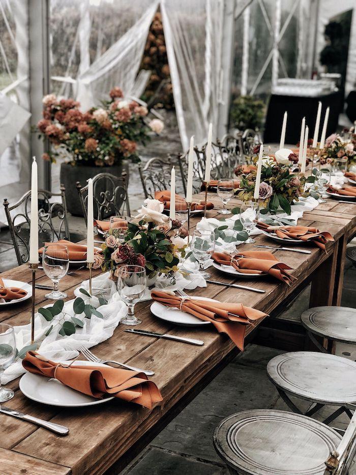 décoration mariage table theme automne avec compositions florales de fleurs marrons, blanc et rose sur table bois brut avec chemin de table voile blanche