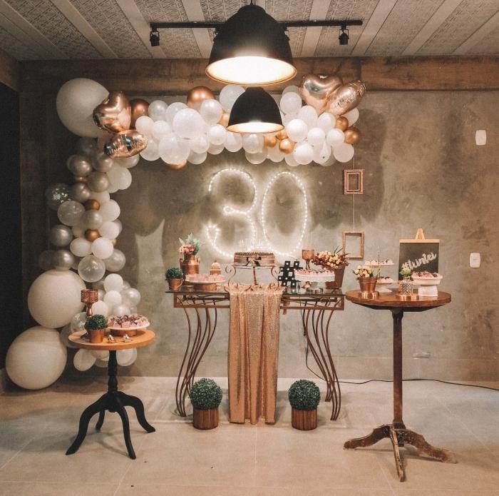 décoration pour une fête d'anniversaire 30 ans femme, pièce aux murs béton décorée avec ballons en blanc et rose gold pour un party 30 ans
