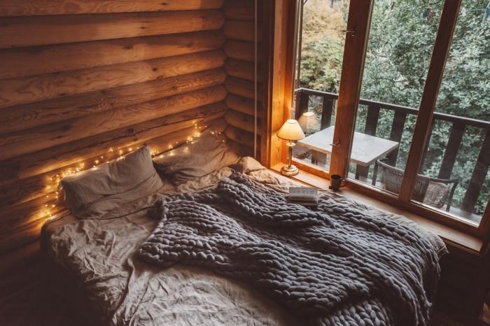 idée déco chambre cozy dans un chalet bois, exemple comment décorer un lit avec gros jeté de lit et guirlande lumineuse