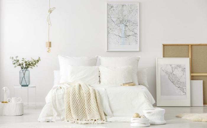 design intérieur scandinave dans une pièce spacieuse aux murs blancs aménagée avec grand lit cocooning à tête de lit bois