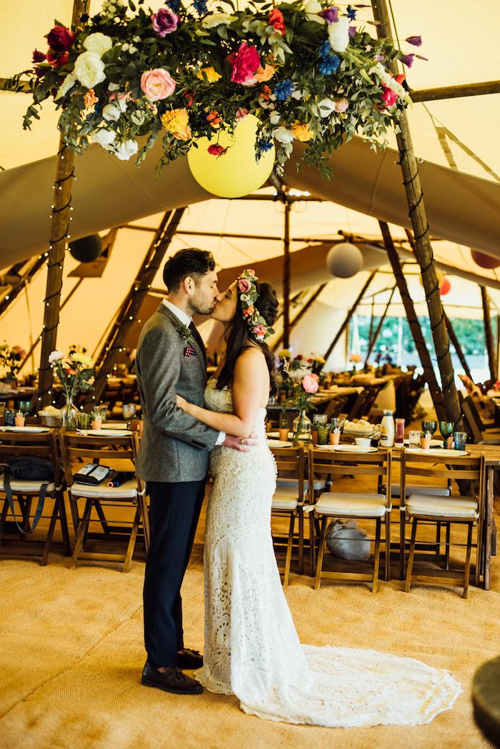 suspension florale géante comme décoration salle de mariage avec tapis fauve, table et chaises bois, tente mariage énorme