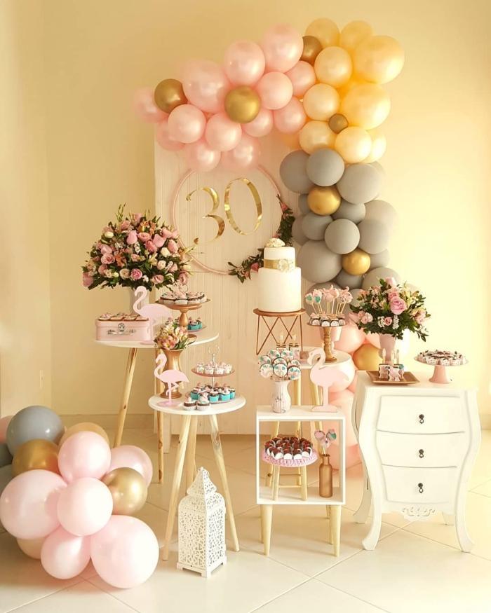 déco d'anniversaire 30 ans femme en rose et blanc avec accents en gris et or, coin festif avec fleurs et desserts