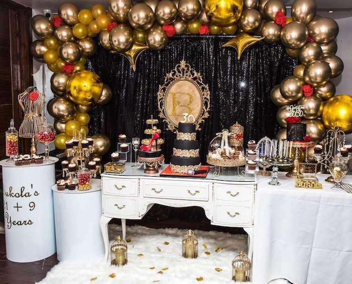 exemple theme anniversaire 30 ans arche de ballons dorés, rideau noir, cupcake, gateau et petites friandises or et noir