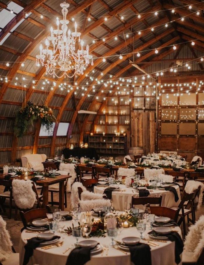 lustre elegant et guirlande lumineuses pour decorer plafond arqué, tables rondes décorées de noir et blanc, centre vegetation et bougies