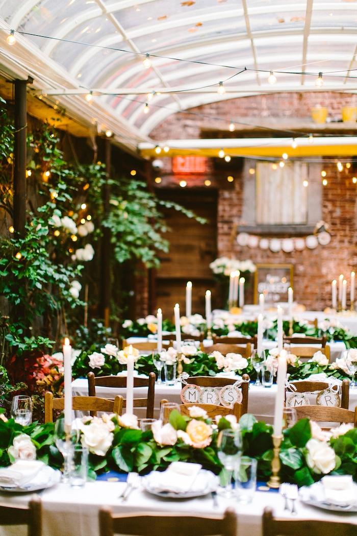 centre de table en guirlande de feuillages verts sur nappe blanche et chaises de bois, deco champetre style garden party