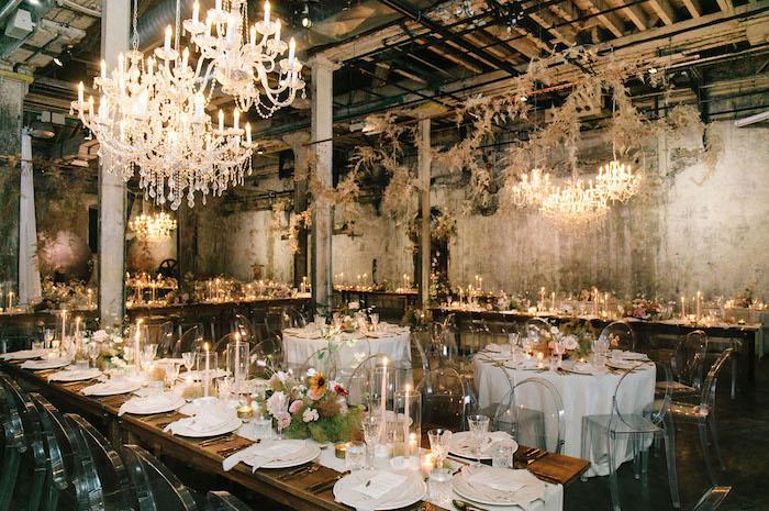 decoration industrielle de mariage dans salle de mariage aux murs bruts, lustres elegantes, chaises transparentes autour de table bois