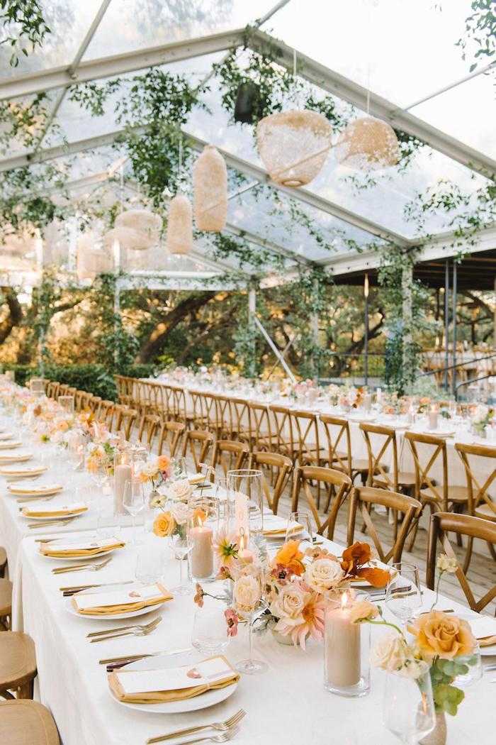 décoration salle de mariage victorienne fleurie avec parois vitrés avec suspensions tressées, bouquets de fleurs au centre, serviette ocre, bougies sur nappe blanche