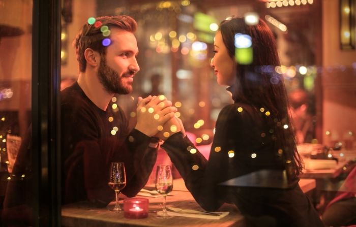 activité en couple pour la Saint Valentin, couple amoureux dans un resto aux grandes fenêtres avec déco de table romantique