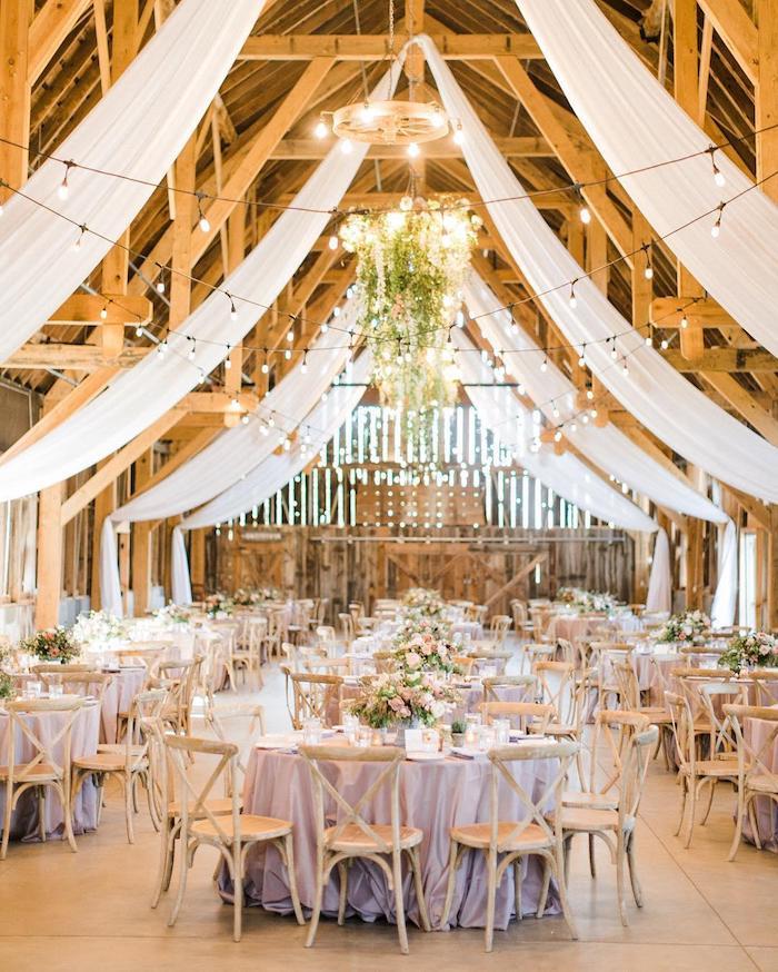 voilages blancs pour décorer une toiture boisée en poutres apparentes, tables elegantes fleuries avec nappes violet clair