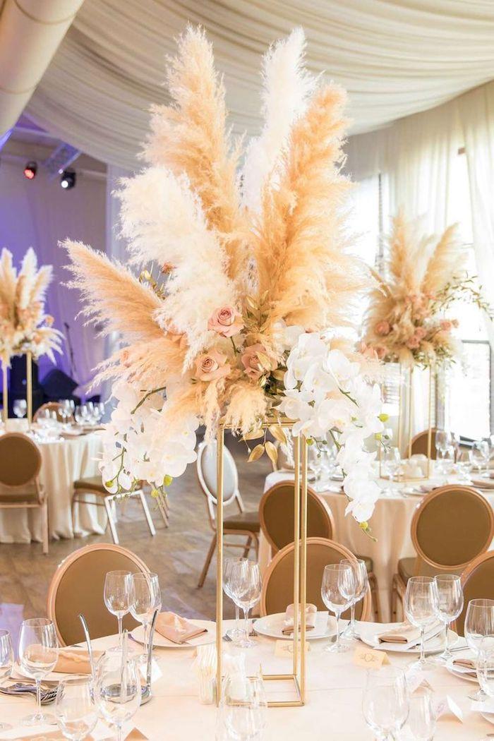composition florale en roses et plumes en hauteur, centre de table original sur table avec nappe blanche, chaises marron