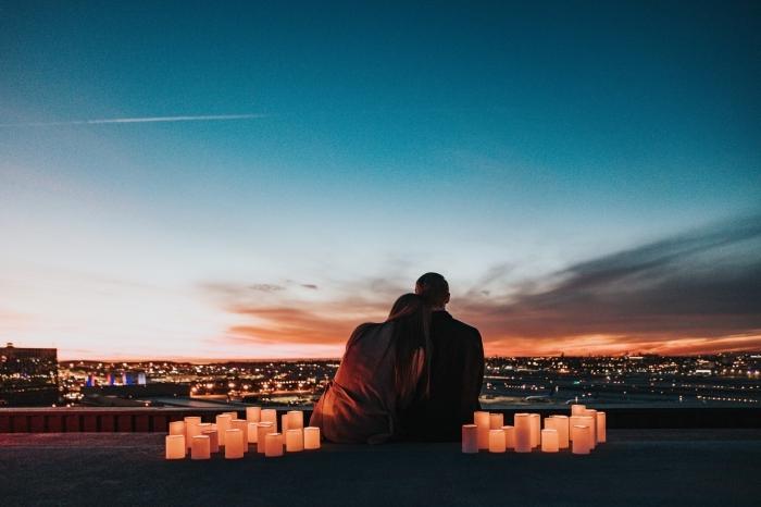 idée d'activité a faire en couple, couple amoureux observant la coucher du soleil au-dessus d'une ville dans une ambiance romantique avec bougies led
