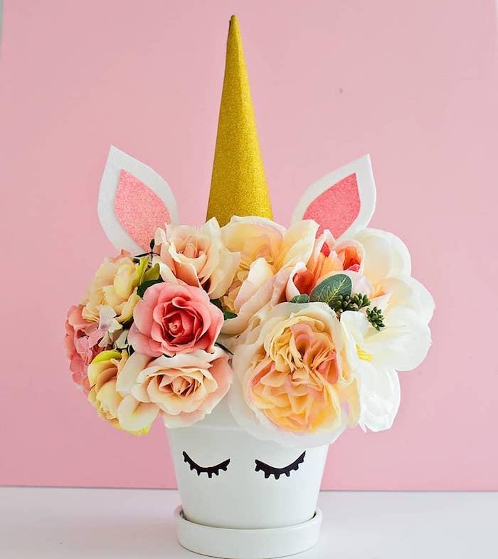 exemple de motif deco licorne sur un pot de fleur blanc, corne de papier or paillette, fleurs colorées, cache pot recup original