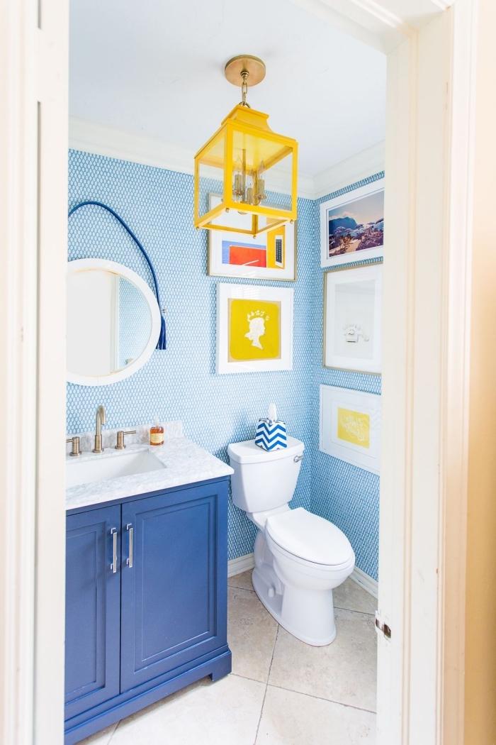 agencement salle de bain petit espace, décoration toilette aux murs bleus avec meubles colorés, décoration murale avec cadres photos