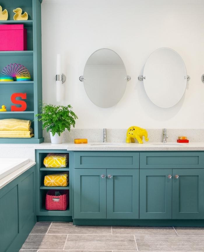 modele de salle de bain blanche au sol gris avec meubles en vert foncé, idée rangement vertical pour salle de bain