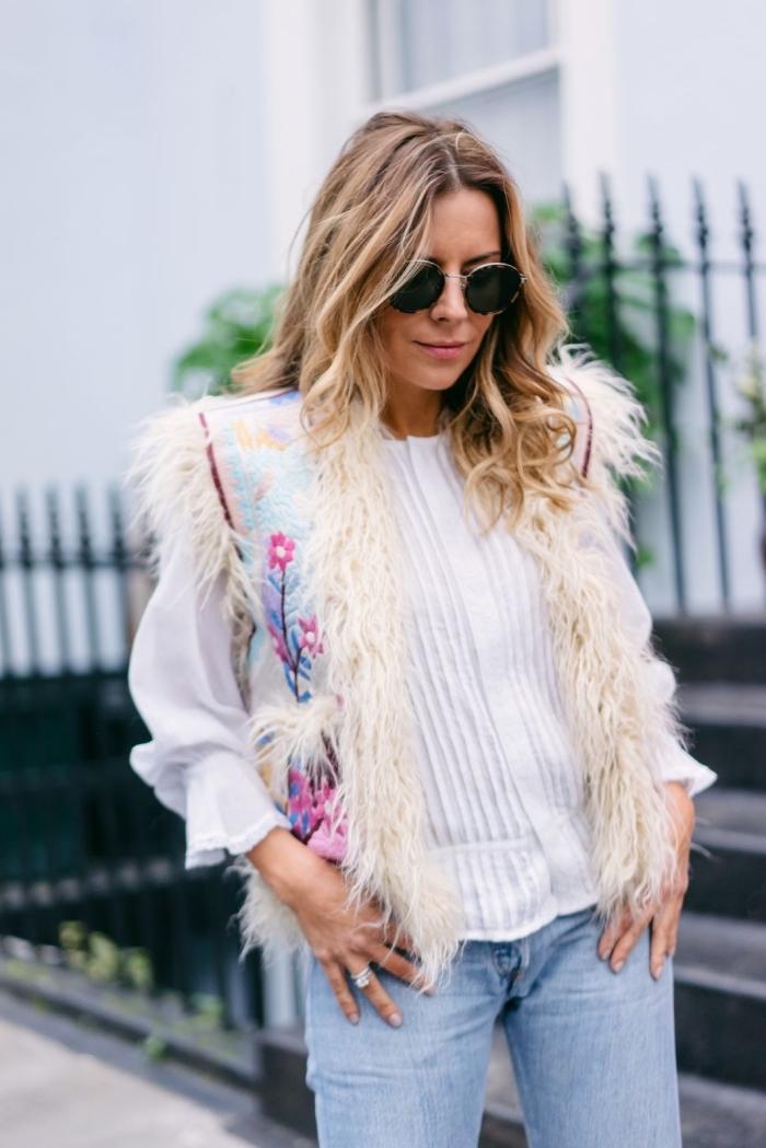idée de look hippie chic femme en jeans clairs et blouse blanche combinés avec gilet en fausse fourrure et détails floraux