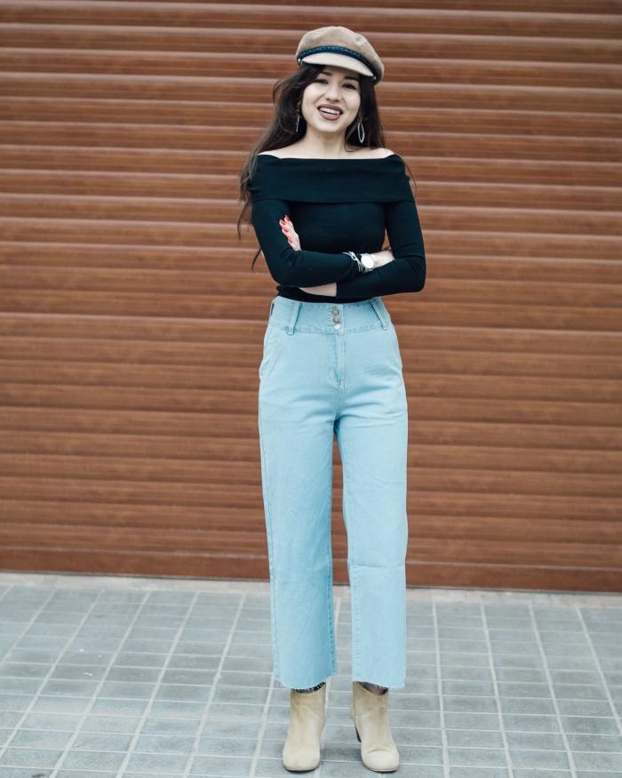 exemple de look année 70 pour femme, tenue en jeans clairs à taille haute avec blouse noire et accessoires beige