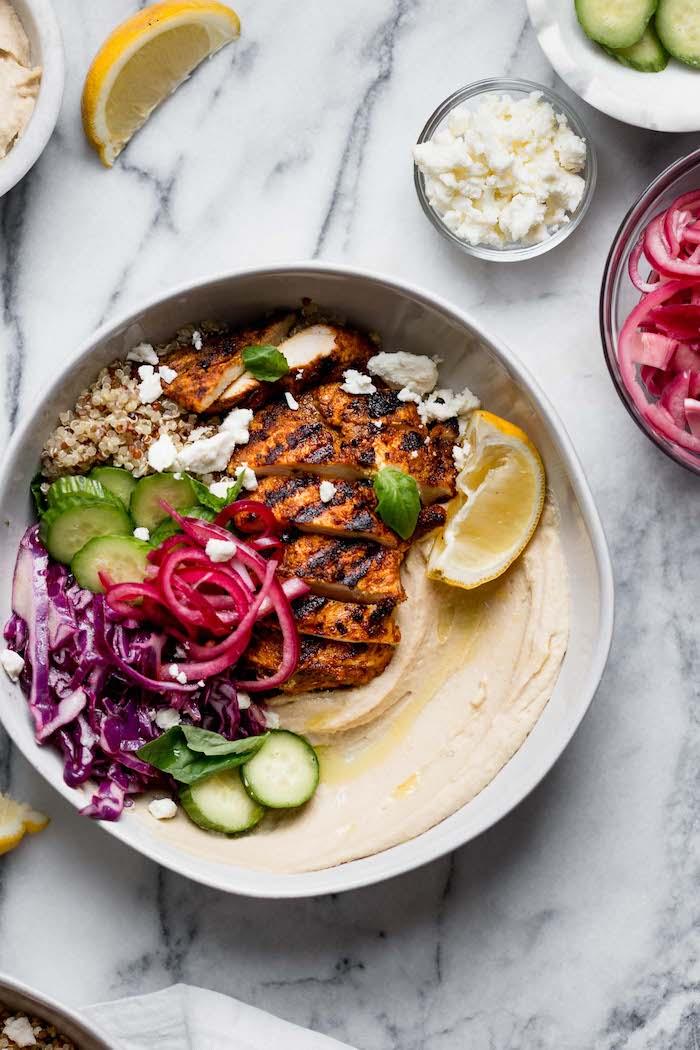 recette de poulet grillé sur canapé de houmous de pois chiche avec salade de chou, quinoa et oignons rouges