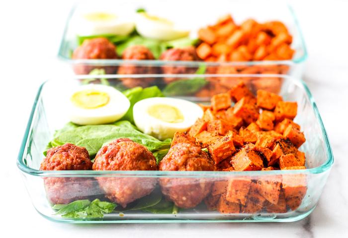 boite de verre rempli de boules de viande à la sauce tomate, oeuf divisé en deux, cubes de patate douce, feuilles de laitue