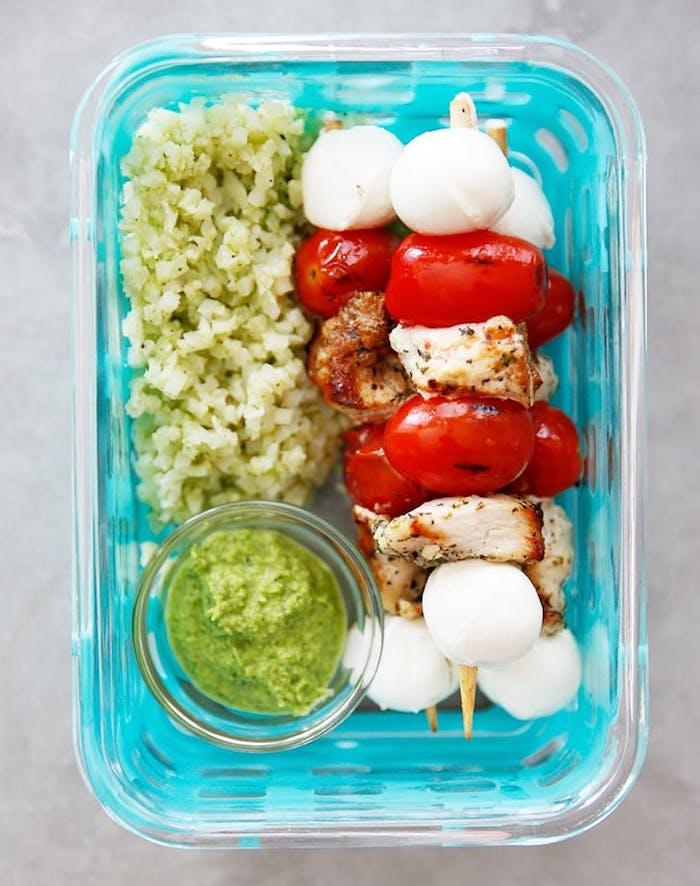 brochette apero façon caprese avec des tomates cerise, boules de mozzarella et des bouchées de blanc de poulet servis avec blé, purée d avocat