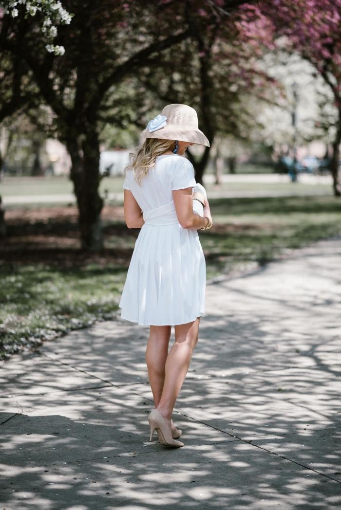 modèle de robe de cérémonie femme chic à longueur genoux accessoirisée avec capeline beige et pochette blanche