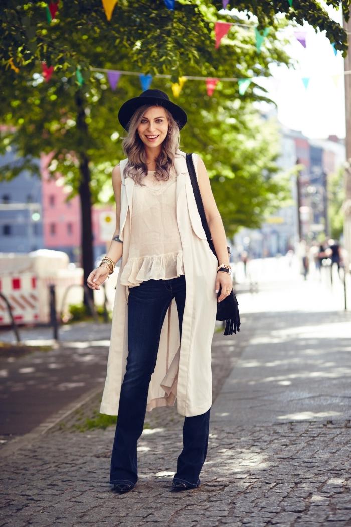 vision hippie chic femme en pantalon évasé foncé avec blouse beige et gilet long accessoirisés avec capeline et sac à franges