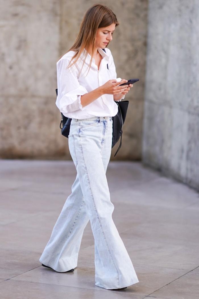 tenue vintage femme aux jeans blancs à taille haute combinés avec chemise à manches courtes et gros sac à main cuir noir