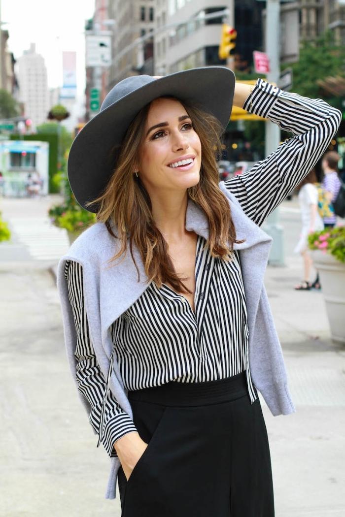 idée de look année 70 en pantalon noir et chemise blanche et noire avec gilet gris et capeline de couleur gris clair