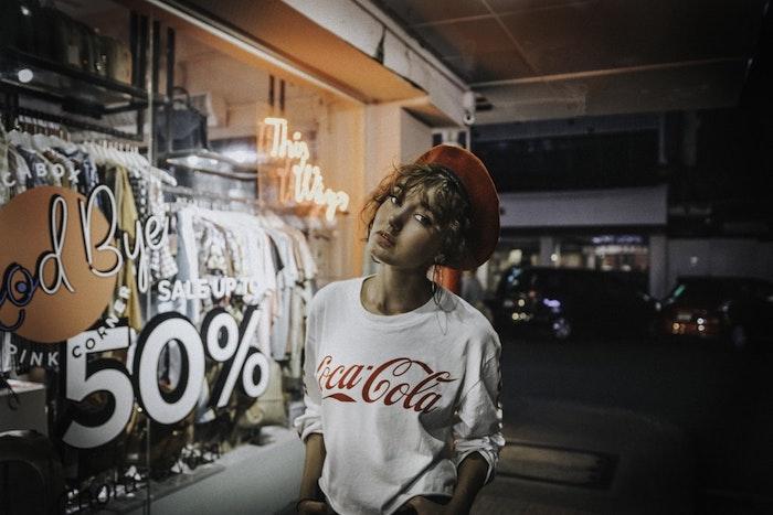 Béret rouge femme cheveux bouclés, blouson blanc avec logo coca cola, style année 90, look années 90 pour soirée, chaussure retro