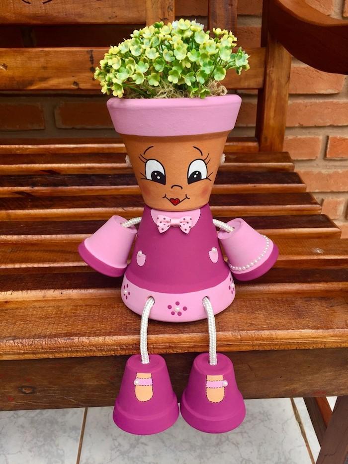 fabriquer des personnages avec des pots de fleurs en rose clair et foncé avec dessin traits de visage sur pot et plante verte a l interieur