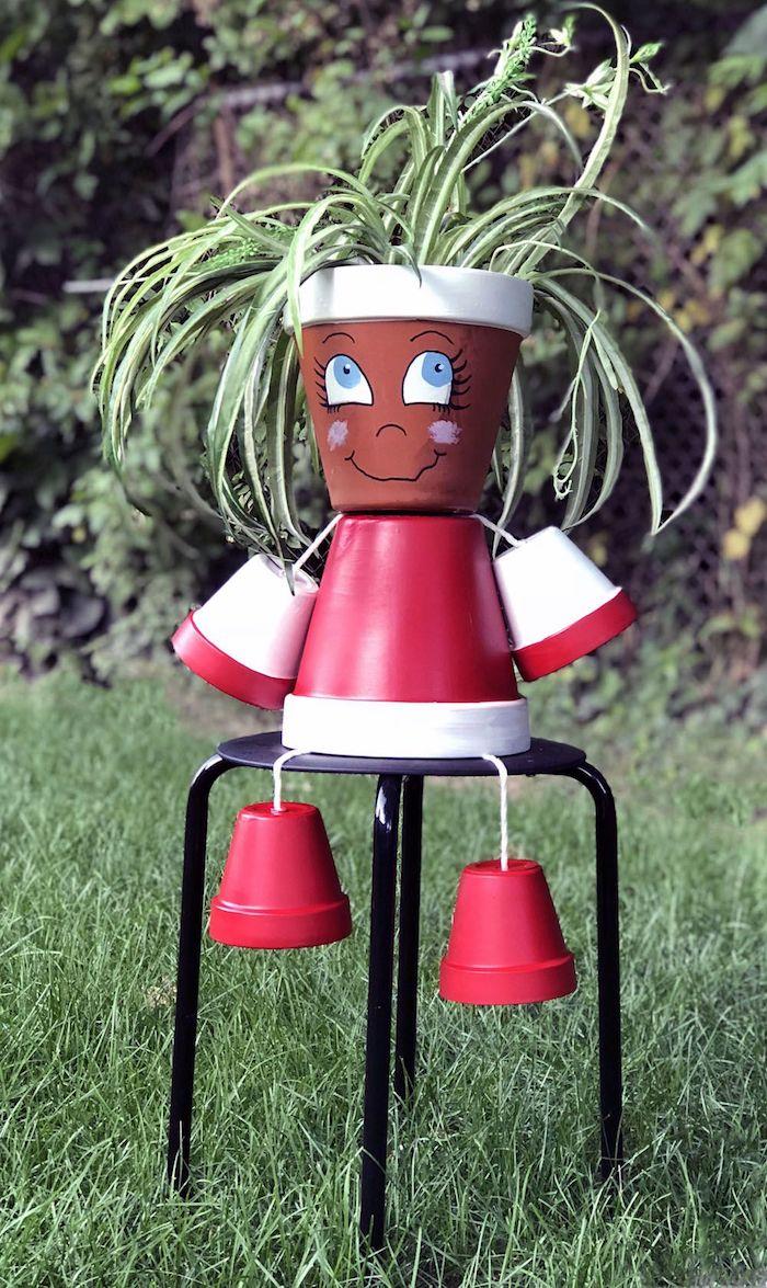 bonhomme en pot de fleur a faire soi meme en pots décorés de peinture rouge et blanche avec dessin traits de visage et plante a l interieur