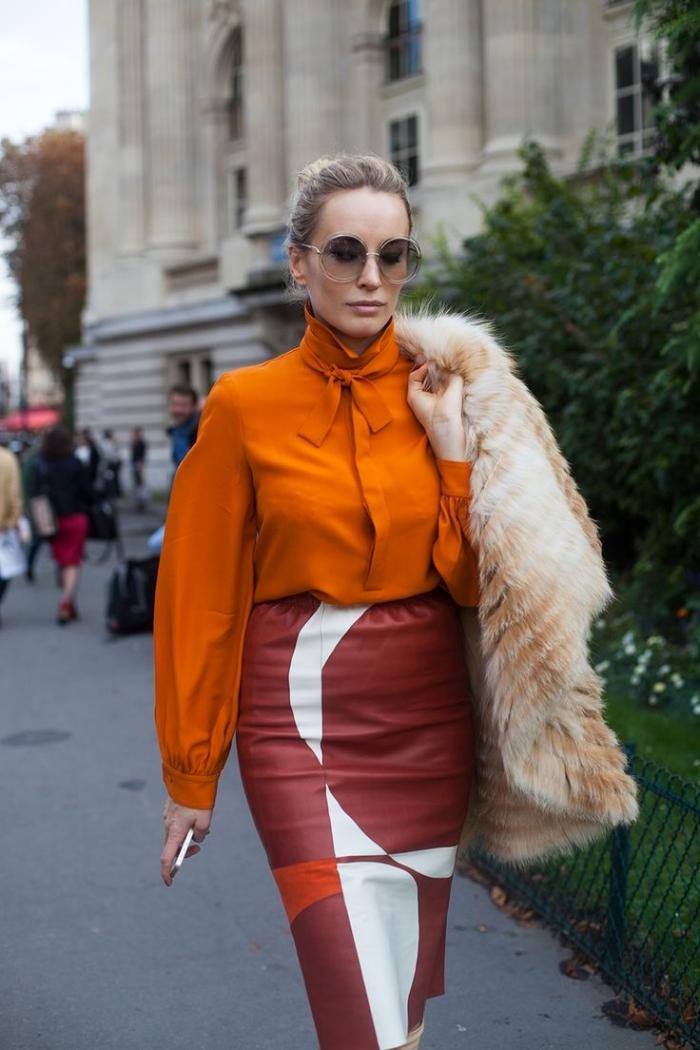 idée de tenue année 70 femme stylée en jupe cuir rouge midi et chemise orange avec manteau en fausse fourrure
