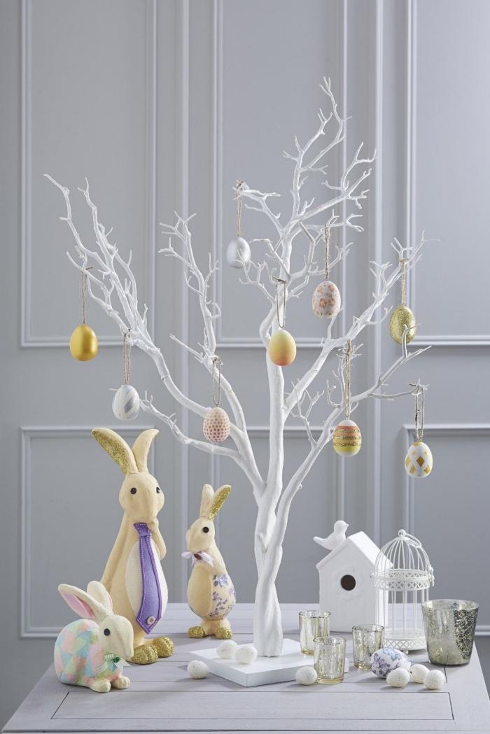 bricolage paques facile à réaliser soi-même, modèle d'arbre minimaliste en branches peintes en blanc et décorés d'oeufs