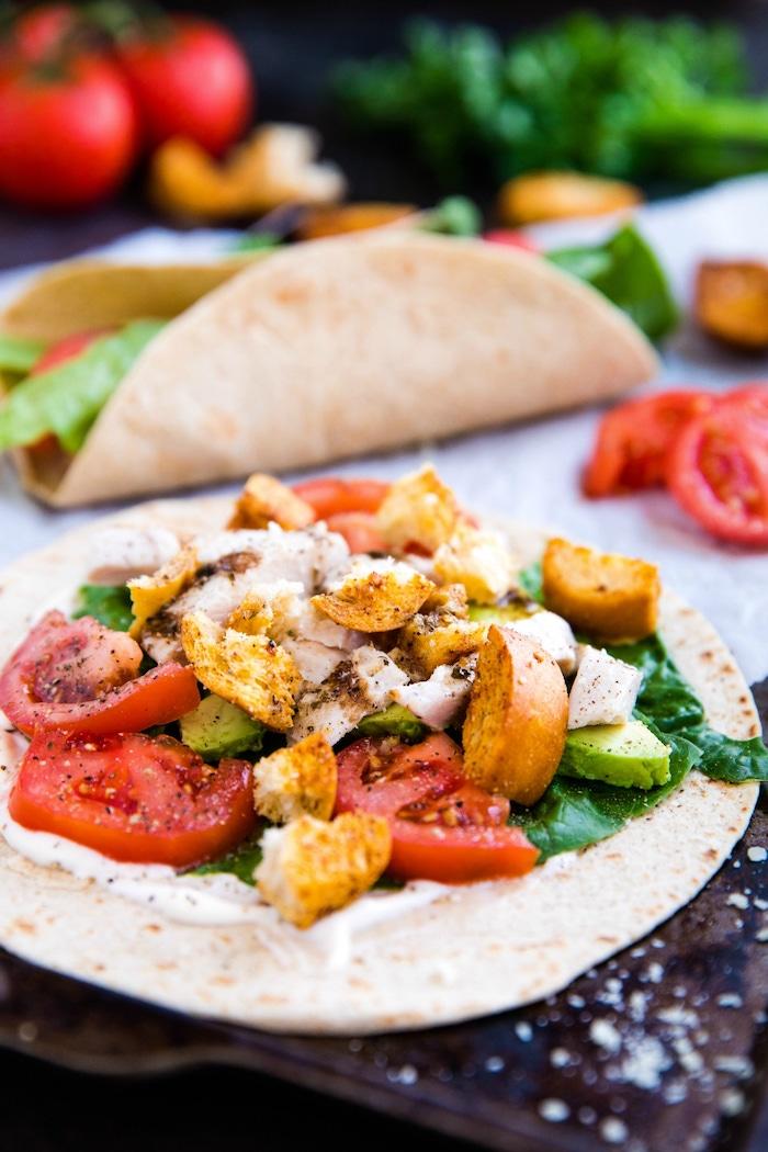 idée de wrap apéro vegetarien avec épinards, tomates, miettes de pain grillé, avocat sur canapé de sauce yaourté