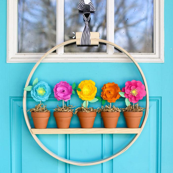 decoration de porte originale, cerceau de bois avec de mini pot de terre avec des fleurs de papier coloré à l interieur