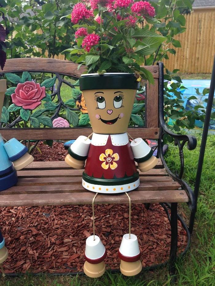idee deco jardin avec recup, pots de fleurs de tailles variées repeints motif bonhomme et plante rose a l interieur