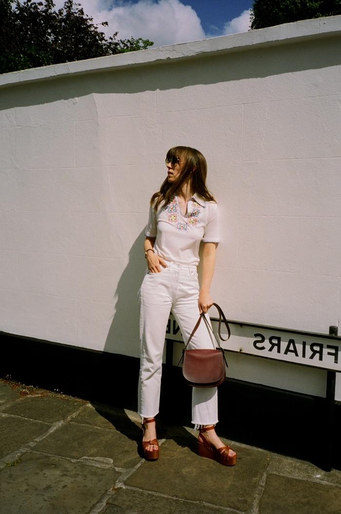 idée de tenue vintage femme en jeans blancs et t-shirt à motifs folkloriques combinés avec sandales marron