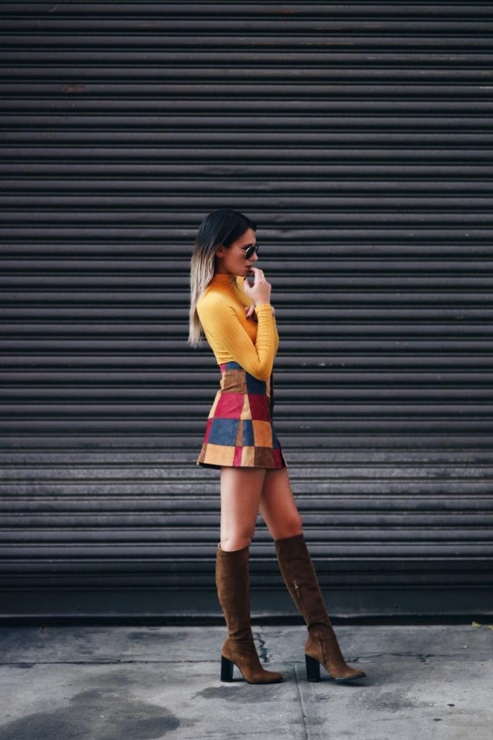 exemple de tenue année 70 en jupe courte à motifs carreaux portée avec pull enroulé en jaune moutarde et bottes marron