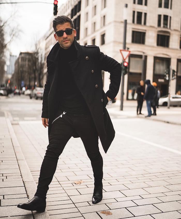 Manteau long noir, pantalon slim noir, tenue homme chic, style glamour pour homme costume lunettes de soleil ray ban