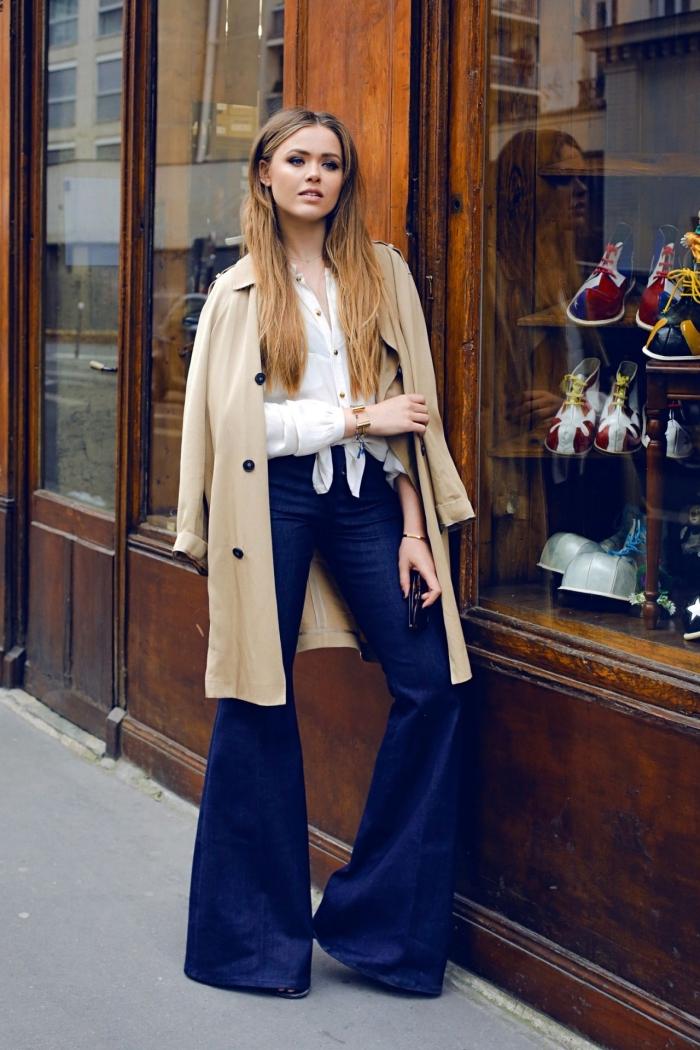 idée contemporaine pour une tenue année 70 femme, modèle de pantalon flare en bleu foncé avec chemise blanche et manteau beige