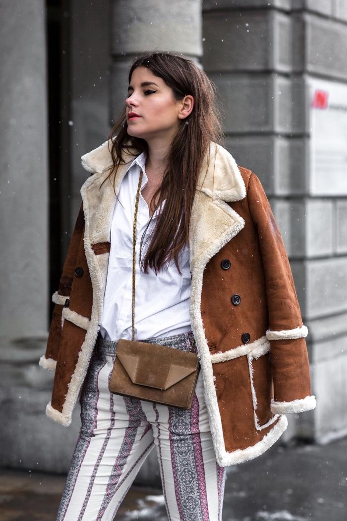 style année 70 pour femme, tenue d'hiver en pantalon blanc à motifs gris et rose porté avec chemise blanche et manteau suède