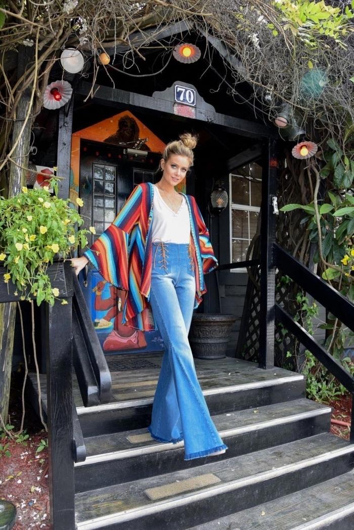 look hippie chic en jeans évasés à taille haute avec blouse à décolleté en v blanche et poncho à manches effet multicolore