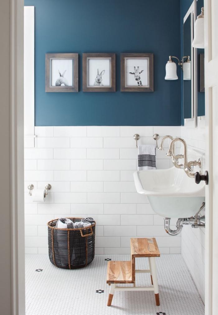 agencement salle de bain aux murs bleu foncé et carrelage blanc, accessoires pour une salle d'eau pour enfant