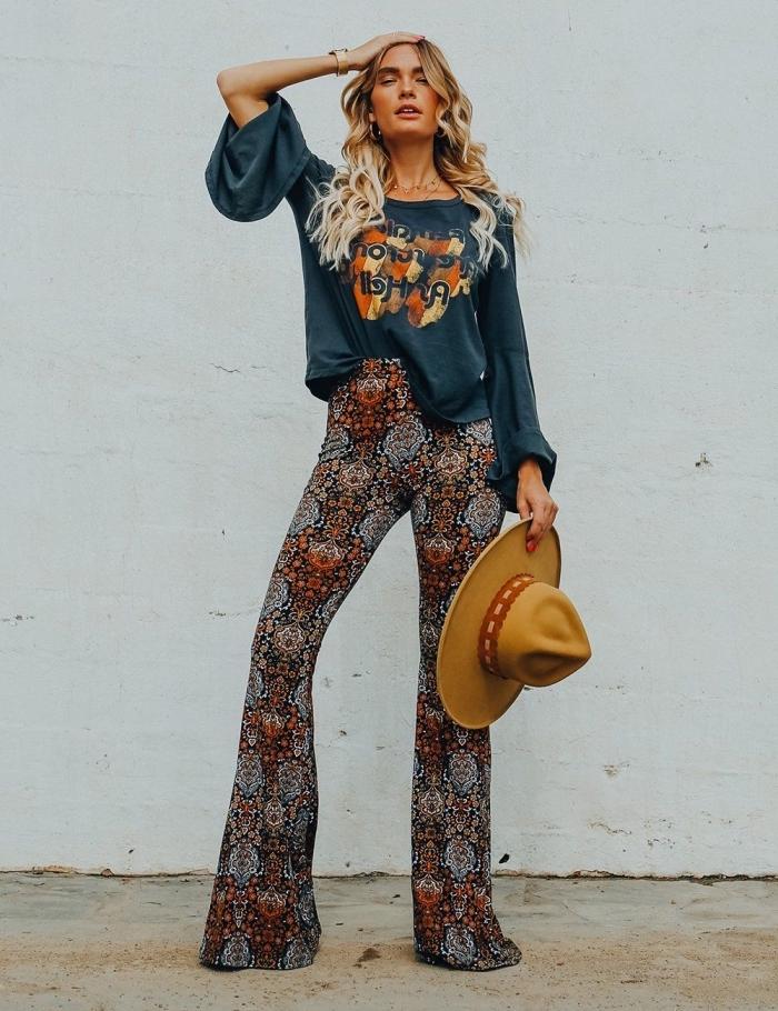 exemple de look hippie en pantalon évasé en noir avec blouse bleu foncé et capeline, vision femme hippie chic