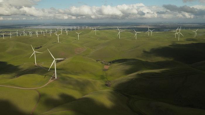 pelouse verte avec une belle vue, nuages en bleu clair et blanc, éoliennes installés sur une grande pélouse