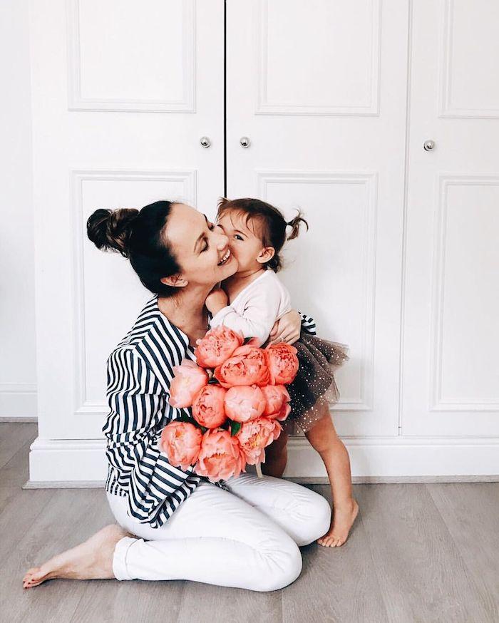 Mere fille photo bisou, bouquet de fleurs pivoines rouges, idée tenues coordonnées pour la mère et son bébé en blanc et bleu
